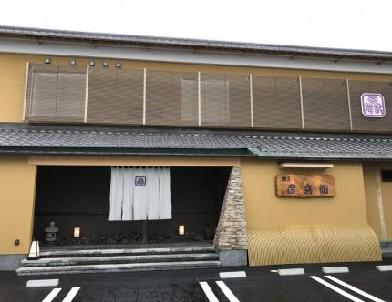 浅い黄色の壁に瓦屋根、犬矢来に二階の格子窓が和を思わせる