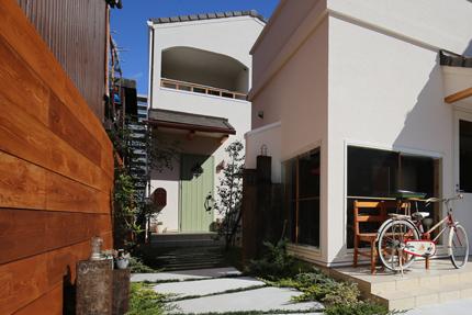 店舗の脇を抜けて住宅の玄関に至るアプローチ。店舗の外壁から突き出した袖壁が住宅の門壁となるデザイン。